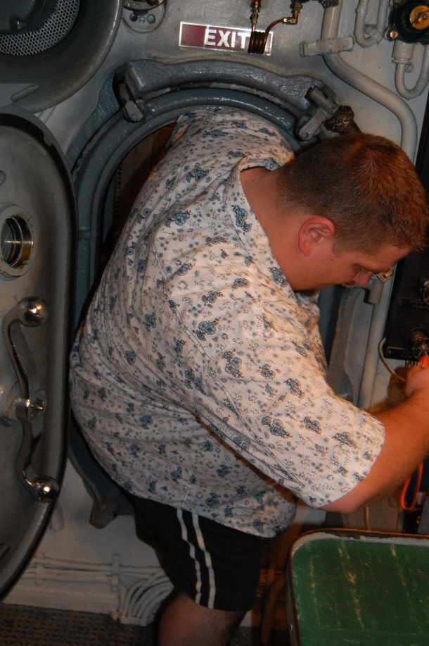Squeezing through a door on the Bowfin Submarine is not easy