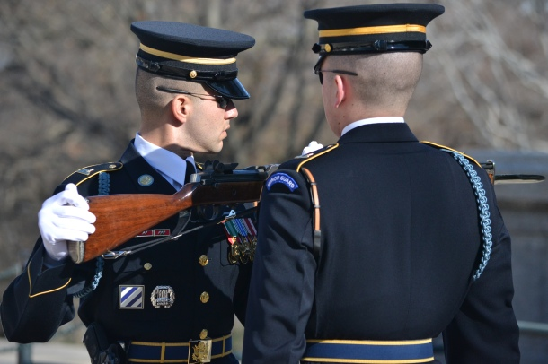 The sergeant inspects the replacement guard's weapon