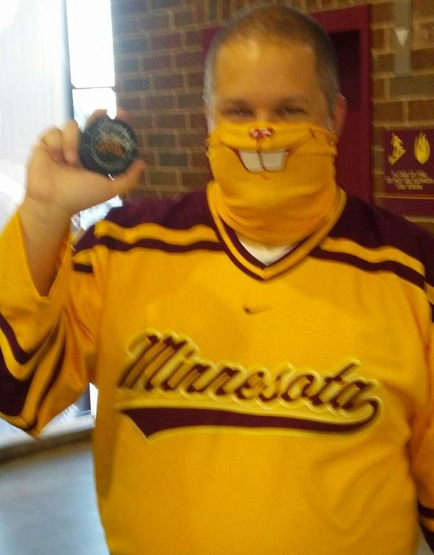 Celebrating Hockey Day in Minnesota with my Gopher mask and autographed puck, thanks to my donation to Defending the Blue Line